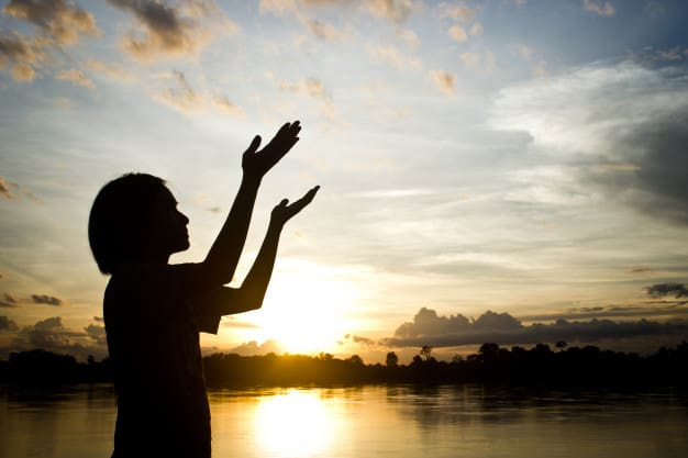 siluetas-mujeres-rezando-entrega-hermosa-puesta-de-sol-de-fondo_3248-2125